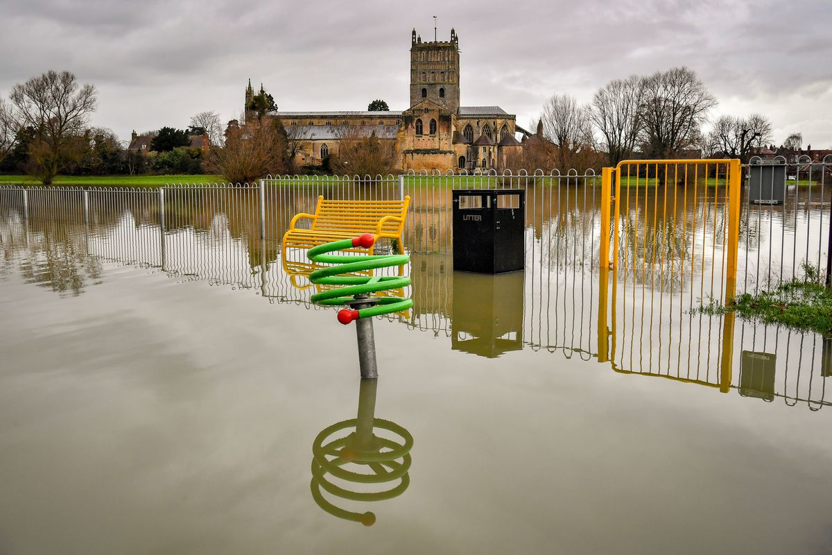 Children's playground equipment pokes out from floodwater surrounding Tewkesbury Abbey