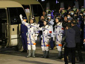 From left, Chinese astronauts Zhai Zhigang, Wang Yaping, and Ye Guangfu, wave before leaving for the Shenzhou-13 crewed space mission at the Jiuquan Satellite Launch Centre