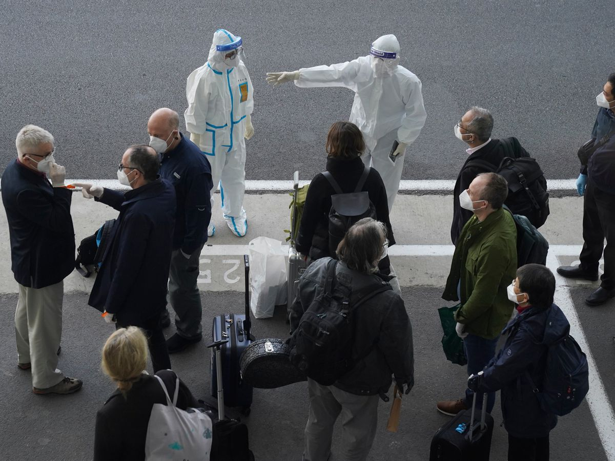 Workers in protective clothes direct members of the WHO team on their arrival in Wuhan