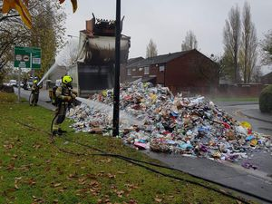 A firefighter doses the pile of rubbish with water. Photo: South Staffs Council