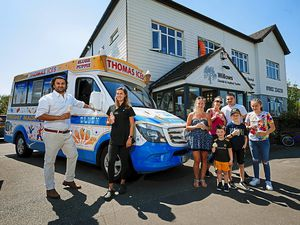 Dentist Neel Barchha and dental nurse Lucy Steel with one of the families who have enjoyed the free ice creams