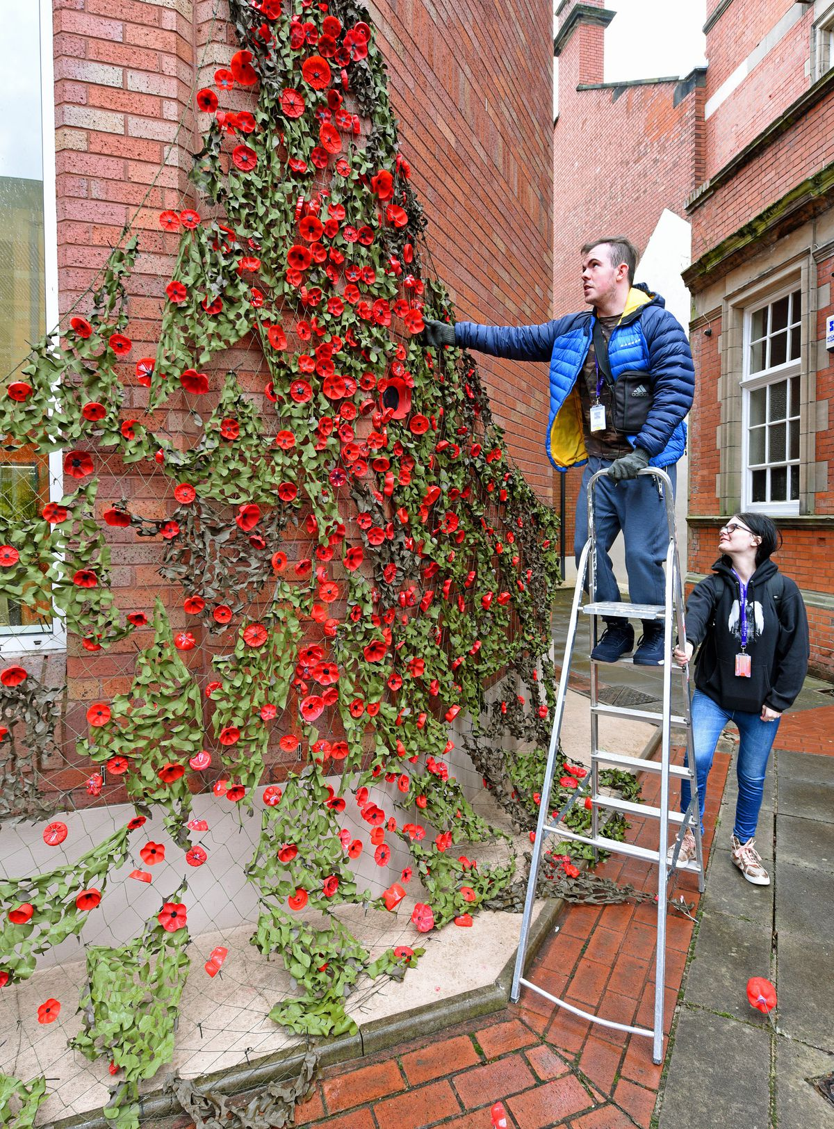 Foundation Studies Creative Arts students next to their poppy display at Stafford College, which were made from plastic bottles. Students Dean Sykes and Sophie Pooler make final adjustments