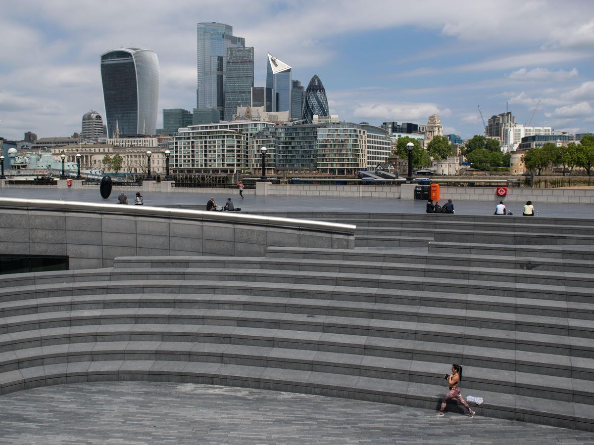 A woman works out on the empty steps of the Scoop, near Tower Bridge