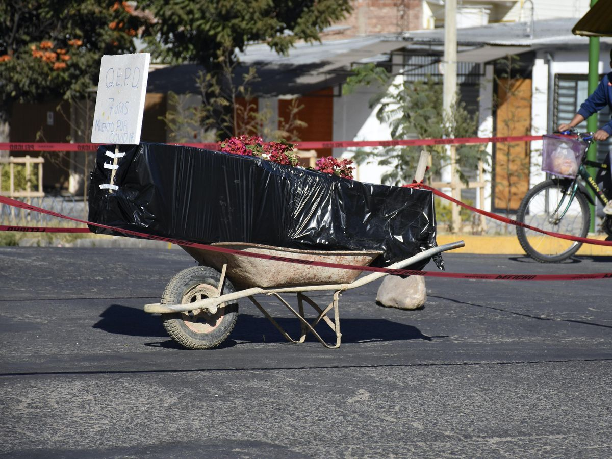 A coffin wrapped in plastic containing the remains of an unidentified men, who died last week, sits on a wheelbarrow in the middle of a street, placed there by his family to draw attention of the authorities to show that his remains are yet to be collected, in Cochabamba, Bolivia (Dico Soliz/AP)