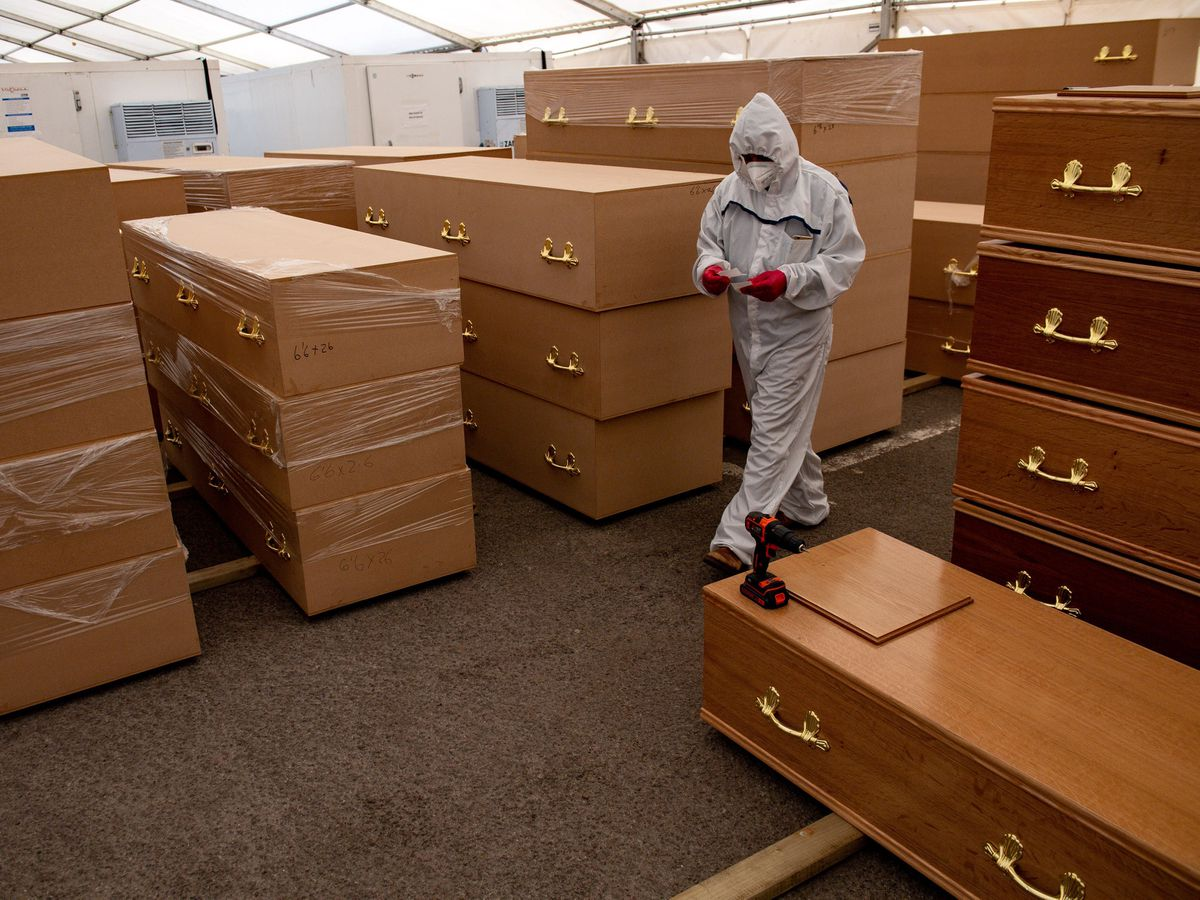 A man walks past coffins