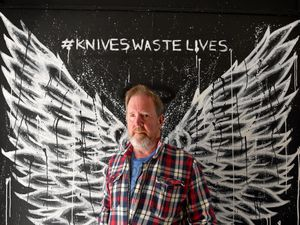 Mark Brindley, father of James Brindley, next to a mural that BW Tattoo Studio in Aldridge