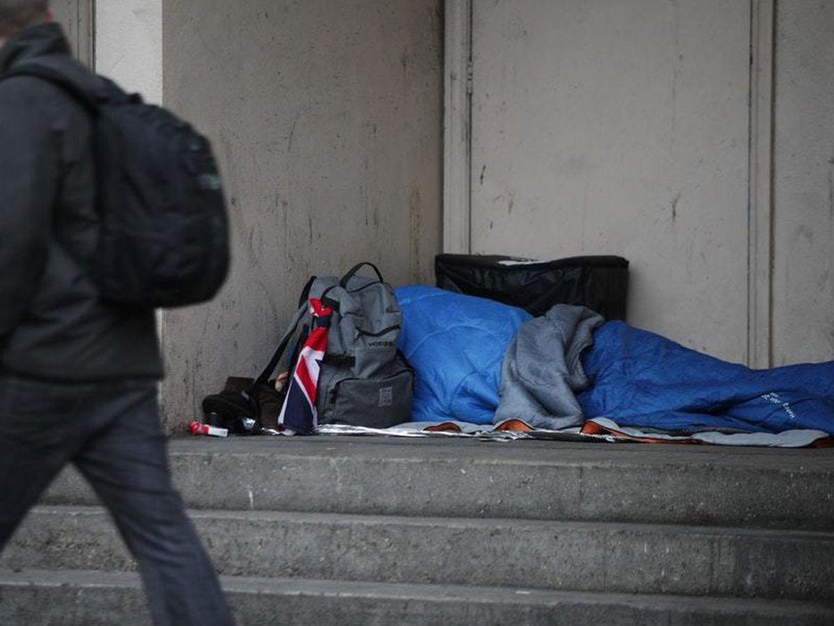 A homeless man sleeps in a doorway