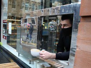 Man handed a coffee through a hatch