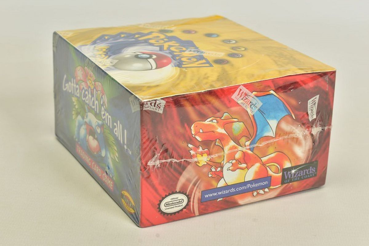 This Pokémon Base Set Booster Box from Wizards Of The Coast has never been opened and is still enclosed in cellophane branded with the WOTC rectangular logo.