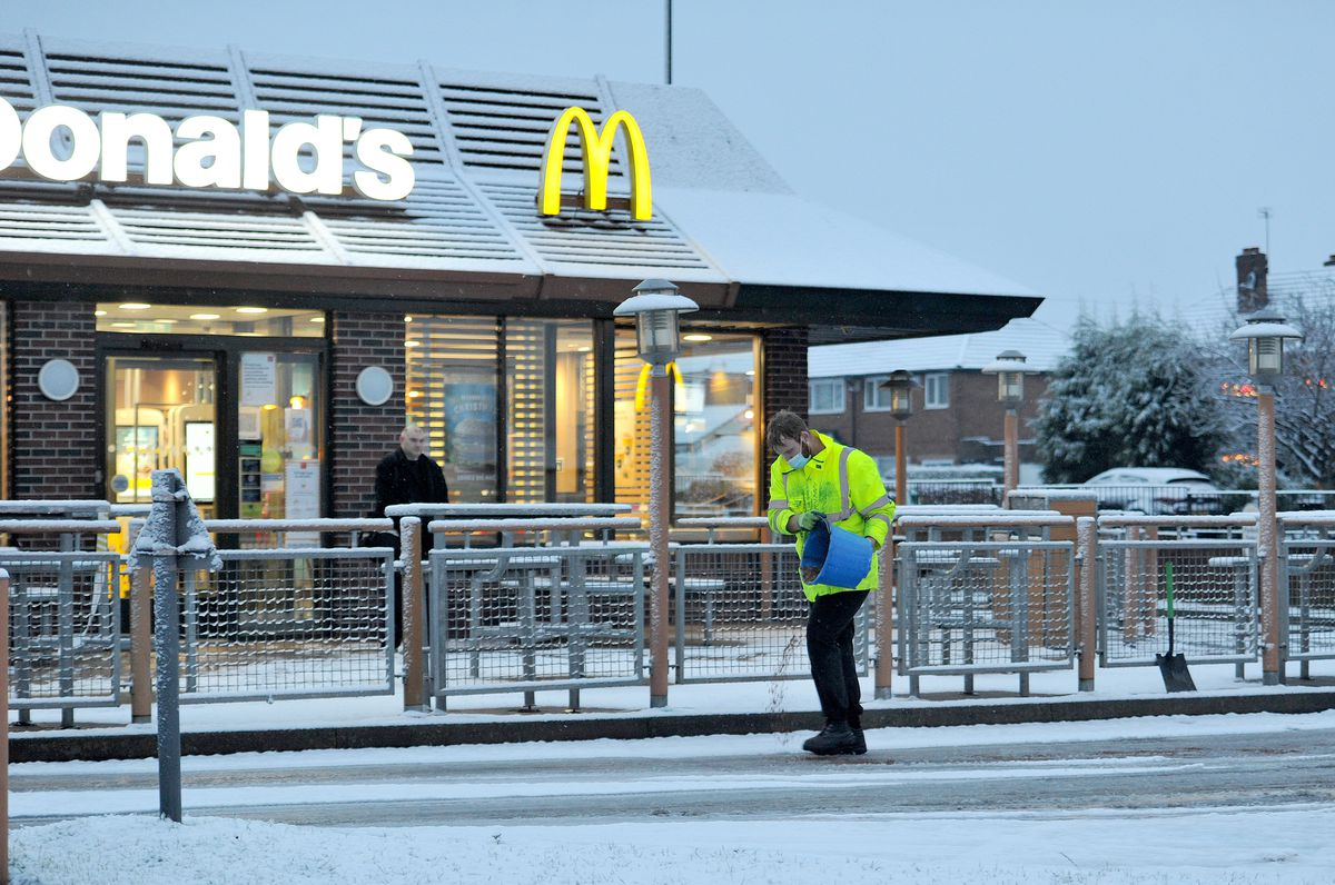 A worker grits the drive-thru at McDonald's, Rushall