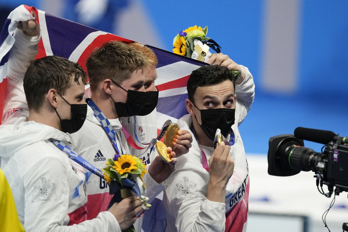 Britain's men's 4x200-meters relay team Tom Dean, James Guy, Matthew Richards, Duncan Scott pose after winning at the 2020 Summer Olympics, Wednesday, July 28, 2021, in Tokyo, Japan. (AP Photo/Charlie Riedel).