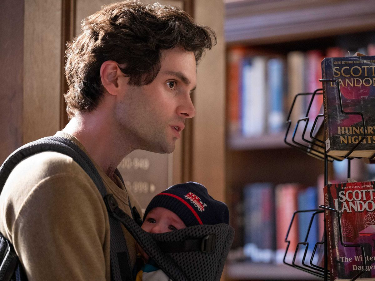 Penn Badgley leans forward while holding a baby in a baby-carrier near a book stand