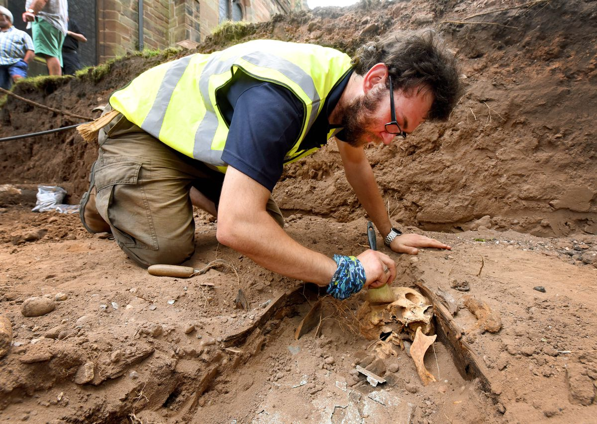 Archaeology dig at St Michael's and All Angels Church, Penkridge. Archaeologist Garreth Davey at work on one of the discovered skeletons in the trench.