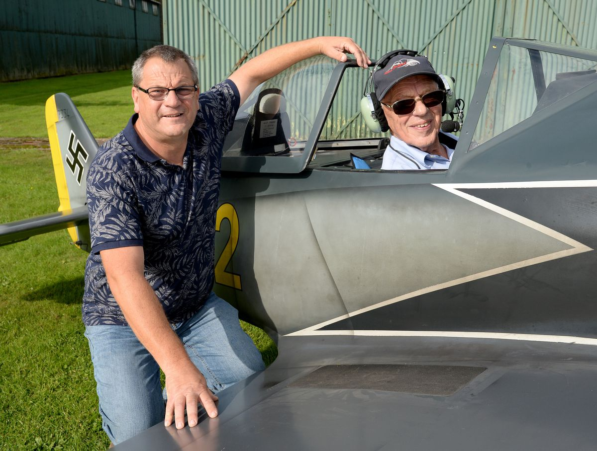 Alan Cottam sitting in the cockpit of a replica Focke Wulf plane, watched by his son Edward