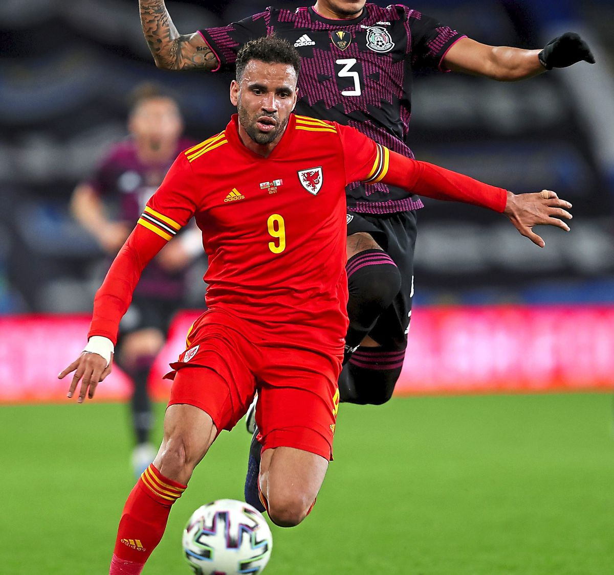 Wales' Hal Robson-Kanu (left) and Mexico's Carlos Salcedo battle for the ball during the international friendly at the Cardiff City Stadium, Cardiff. Picture date: Saturday March 27, 2021. PA Photo. See PA story SOCCER Wales. Photo credit should read: David Davies/PA Wire. Use subject to restrictions. Editorial use only, no commercial use without prior consent from rights holder.