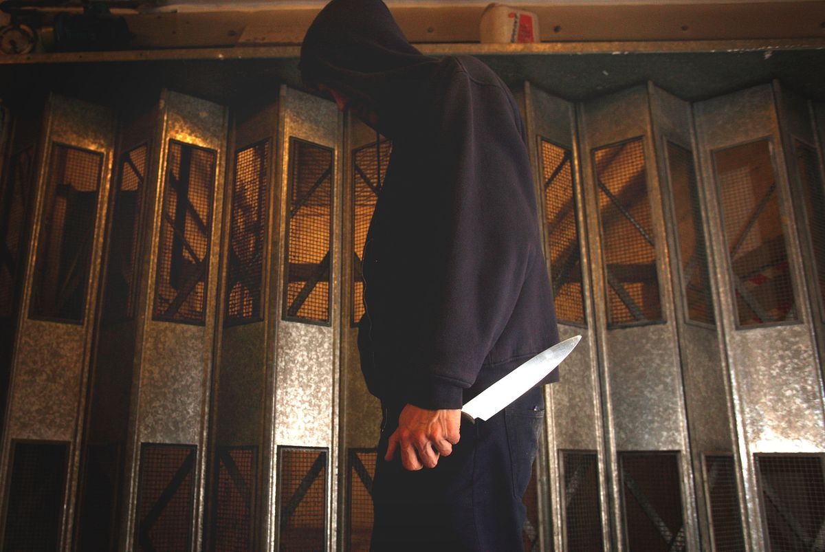 Undated file photo of a person in a hoodie holding a knife.