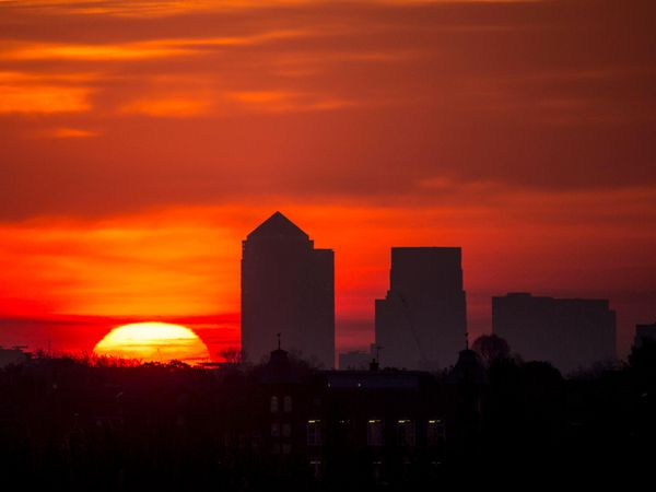 The early morning sun rises behind the Canary Wharf skyline