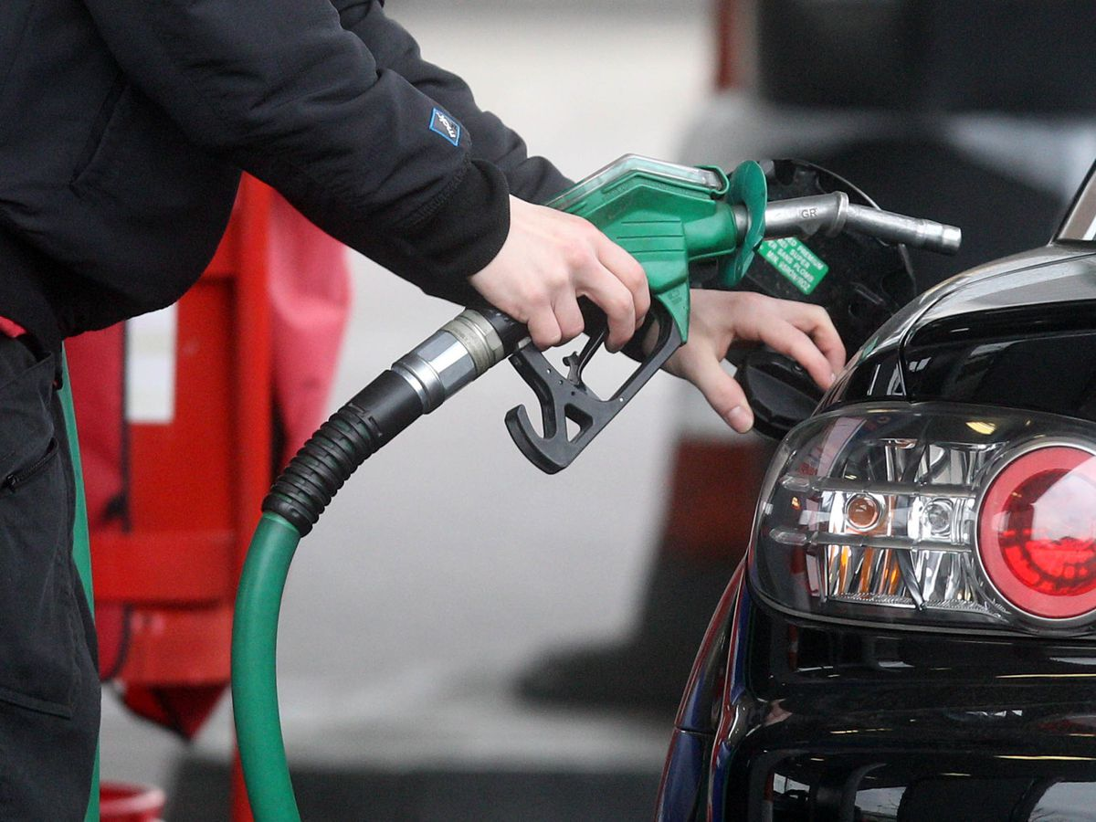 File photo dated 22/02/13 of a person using a petrol pump. According to FairFuelUK savings worth an estimated £145 million were denied to drivers in the past month because fuel retailers failed to pass on cuts in wholesale prices.