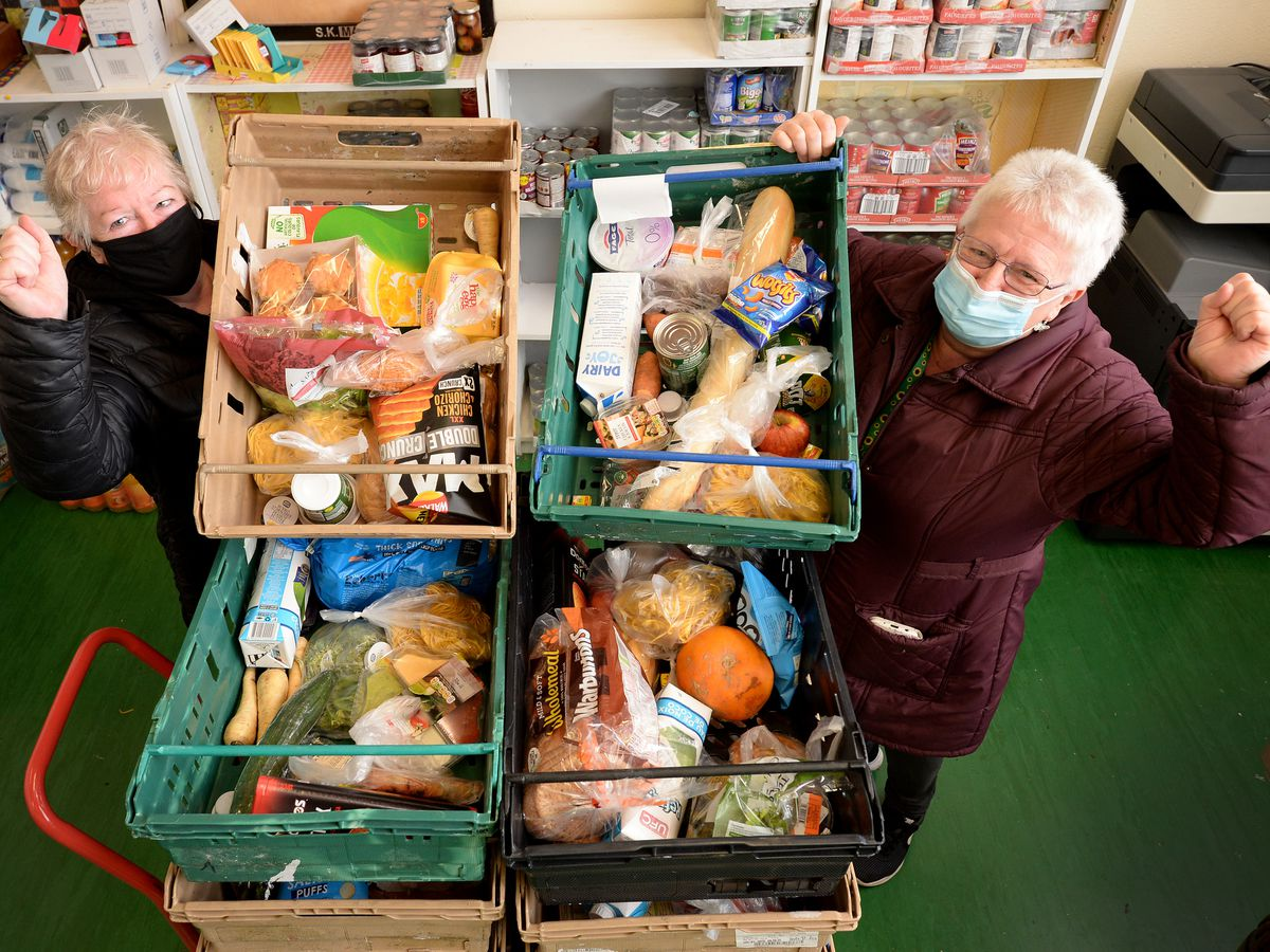 Volunteers Anita McBennett and Brenda Butler with some of the food boxes destined for the needy
