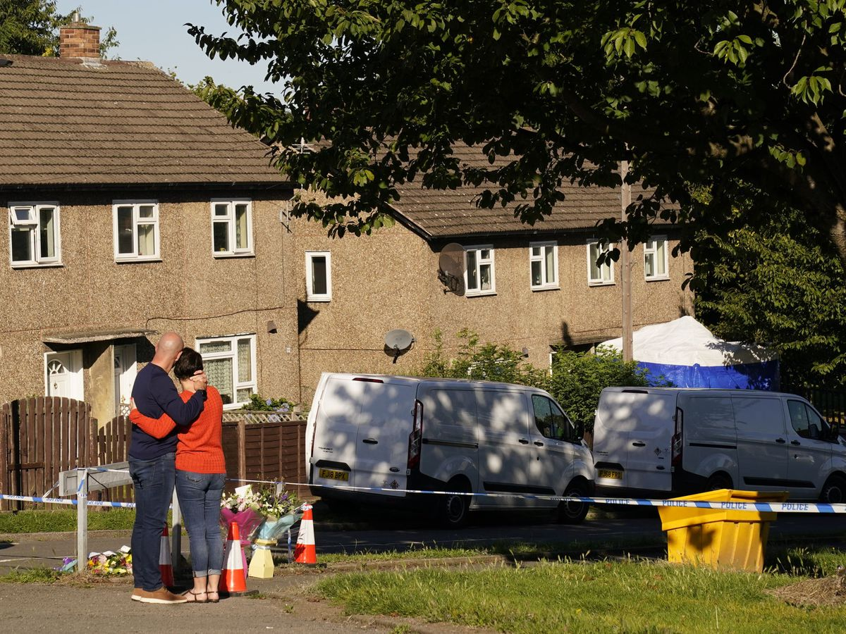 The father to some of the victims leaves flowers at the scene in Chandos Crescent, Killamarsh, near Sheffield, where four people were found dead at a house on Sunday