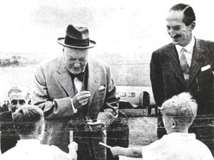 Four-year-old Richard Hill, left, hands a cigar to Winston Churchill as he arrived at Wolverhampton in 1949