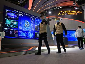 Workers pass by the logo for Alibaba