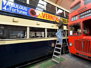 Sign writer Steve Evans puts the finishing touches to signs on the buses at Aldridge Transport Museum