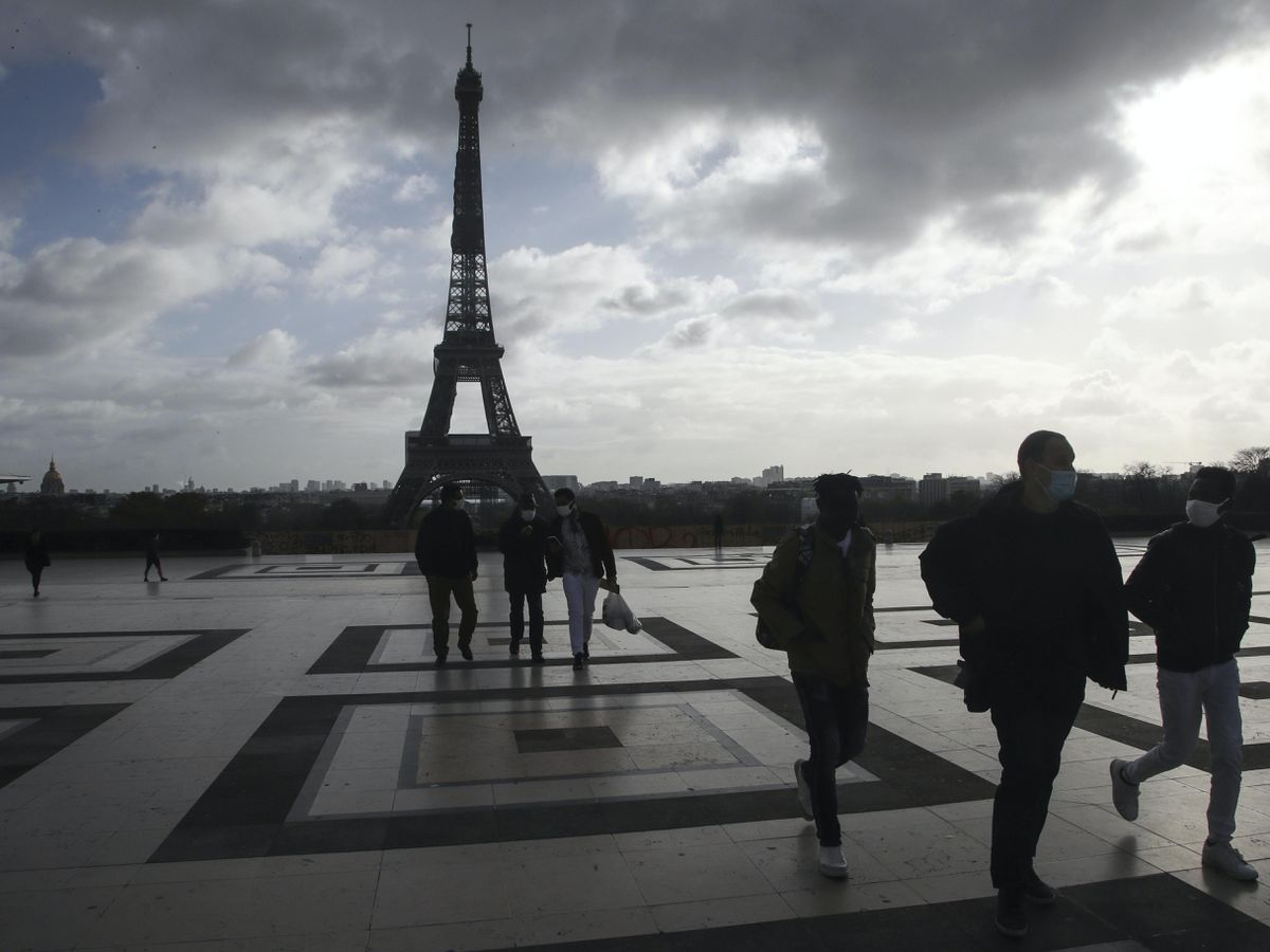 People wearing face masks make their way on the Trocadero square, near the Eiffel Tower (Michel Euler/AP)
