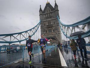 Runners wearing London Marathon running numbers cross Tower Bridge