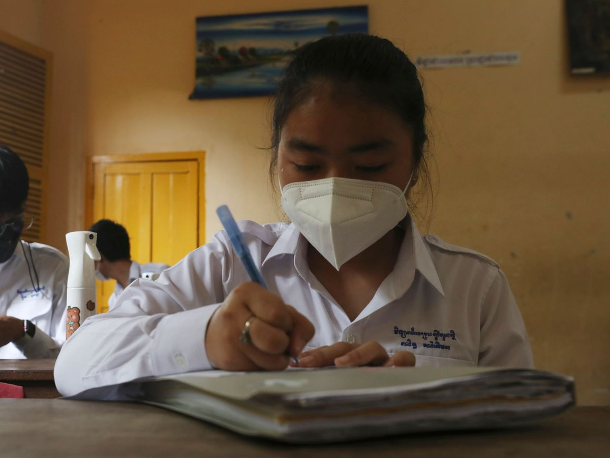 Students socially distance as they sit in a classroom at a high school in Phnom Penh, Cambodia