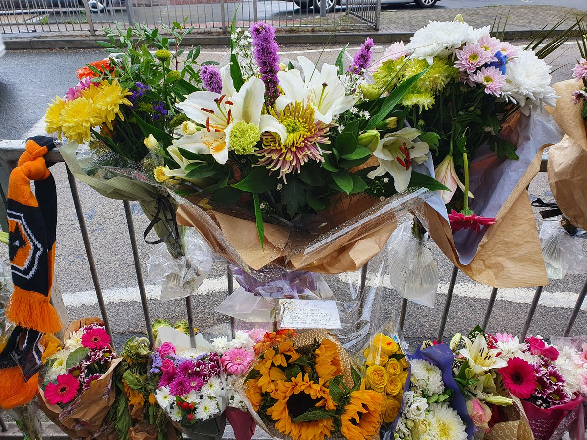 Some tributes have been laid on the ground, while others were tied to the railings