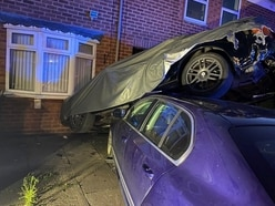 House left damaged as crash upends parked car
