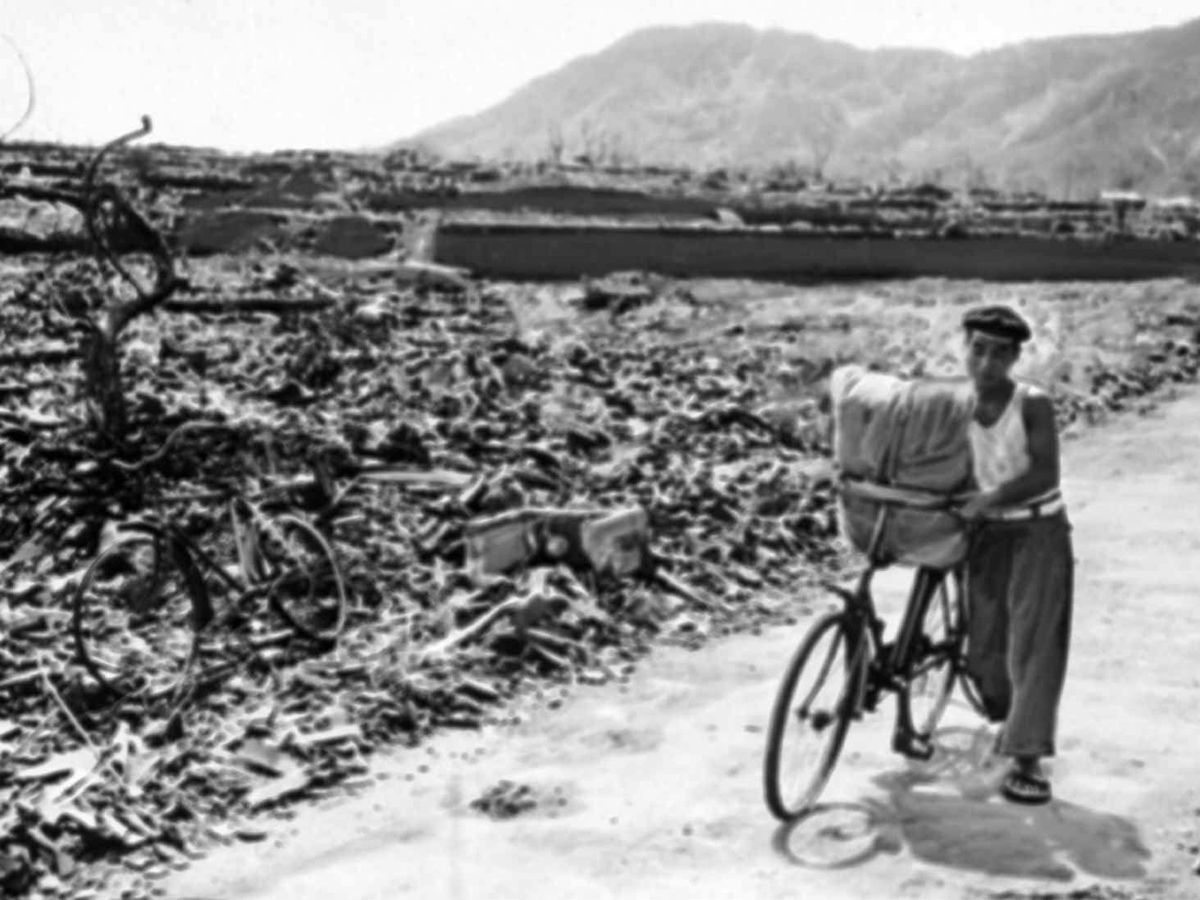 A man pushes his loaded bicycle down a path that had been cleared of rubble after the atomic bombing of Nagasaki, Japan, on August 9 1945