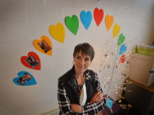Looking at the 'memory tree', showing people who have passed away during the lockdown period, is community development worker Debbie Tye,