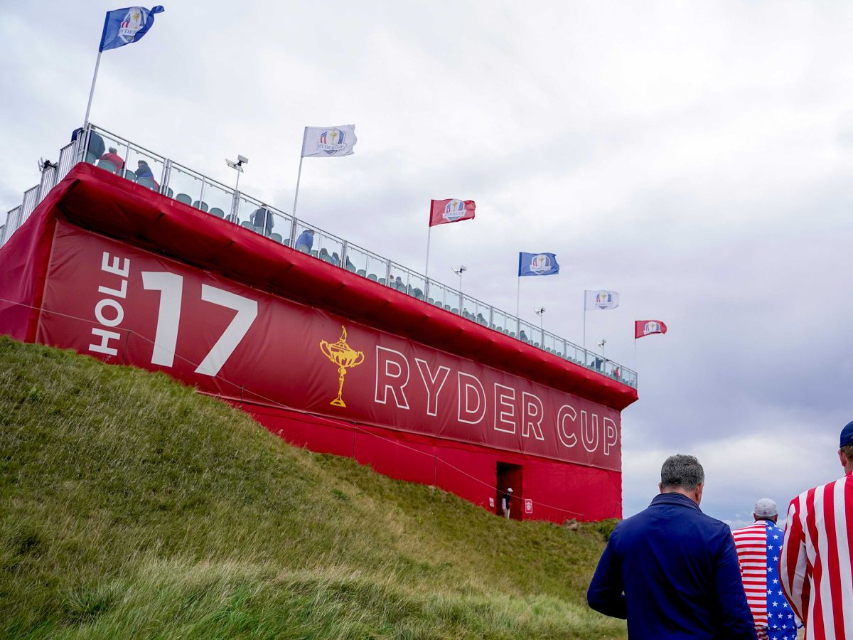 American fans walk past a grandstand on the 17th hole