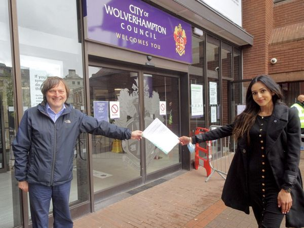 Councillor John Reynolds with Kiran Kular handing over the petition