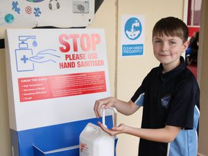 Beacon Hill Academy pupil Jarrod Tully uses one of the school's hand sanitiser stations
