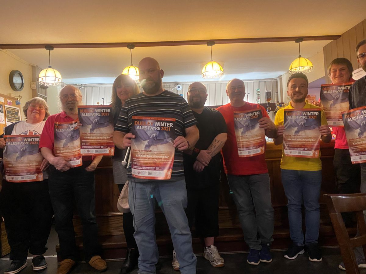 Karl Denning, centre, and branch members display the festival poster