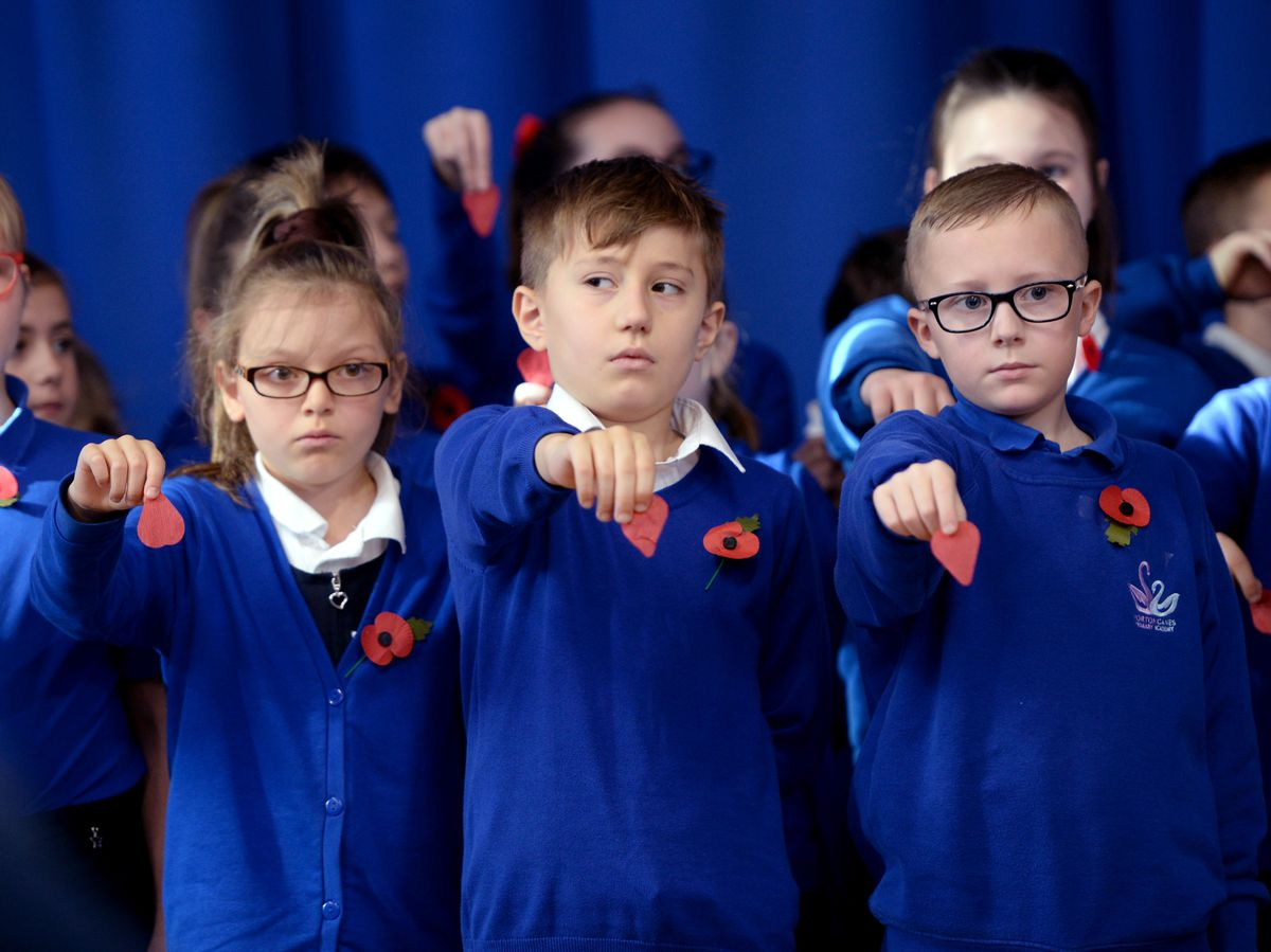 Children prepare to drop poppy petals as names of the fallen are read out