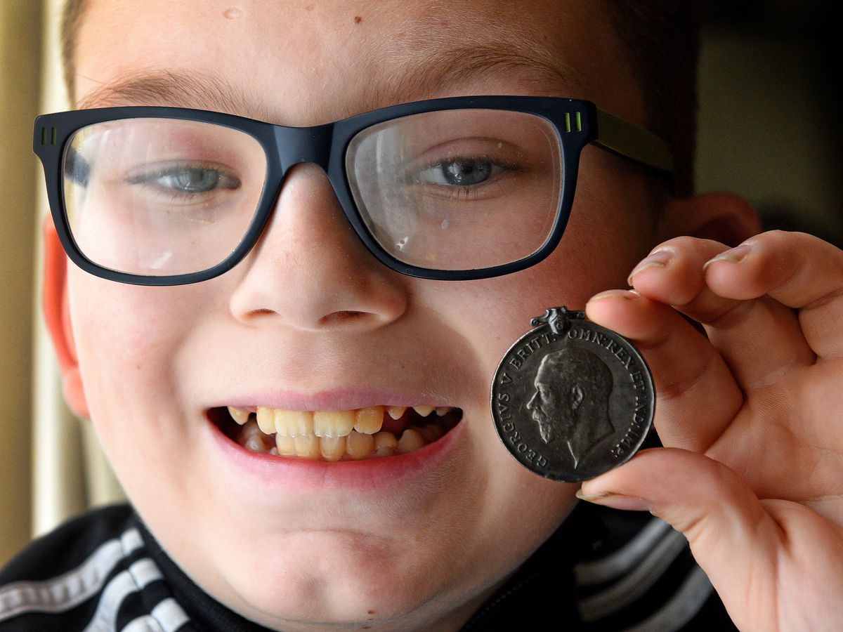 Finley Hargood with the medal he found