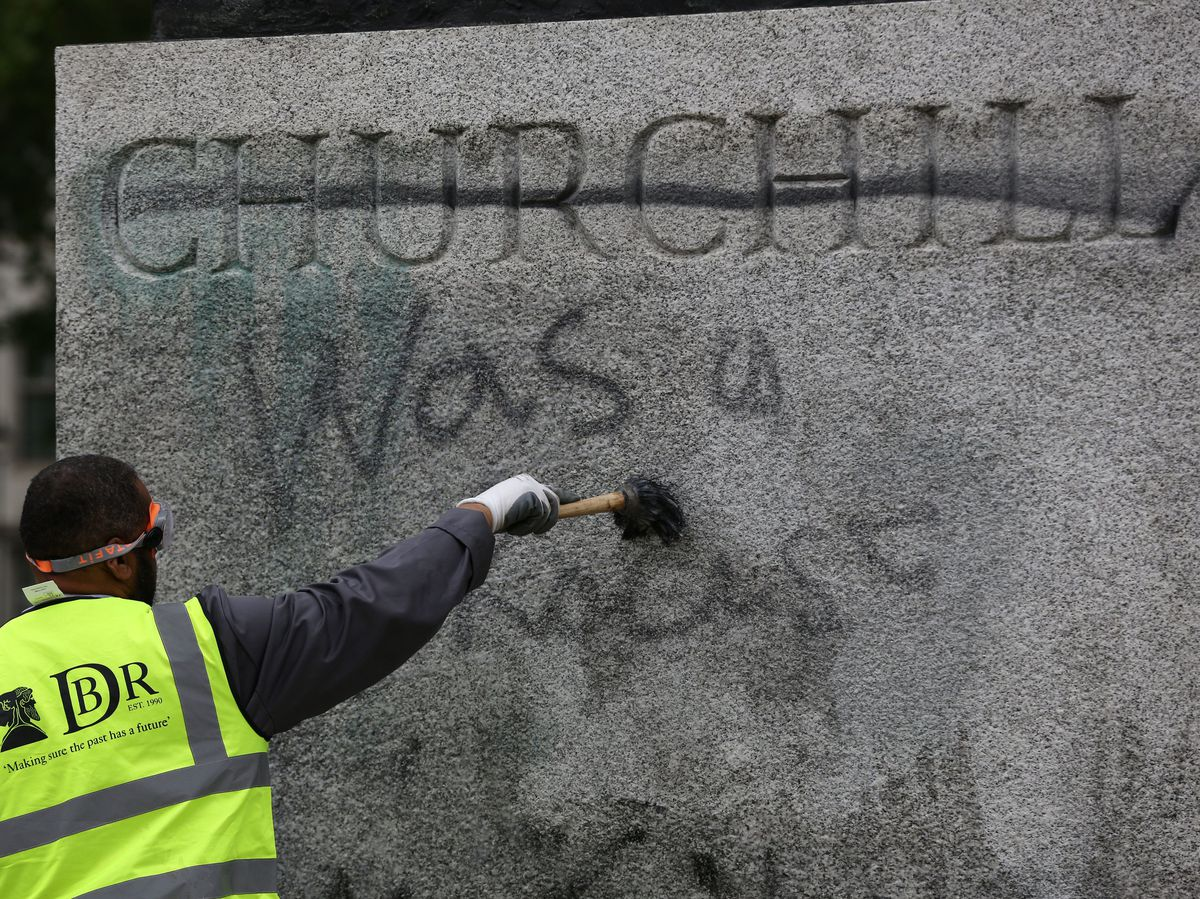A worker cleans graffiti from the plinth of the statue of Sir Winston Churchill in Parliament Square