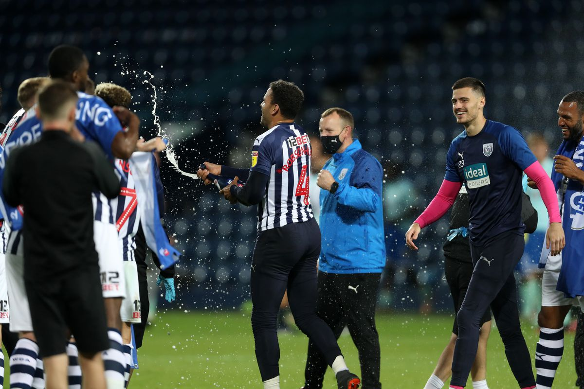 Hal Robson-Kanu of West Bromwich Albion sprays champagne as he celebrates promotion to the Premier League on the pitch at the end of the match. (AMA)