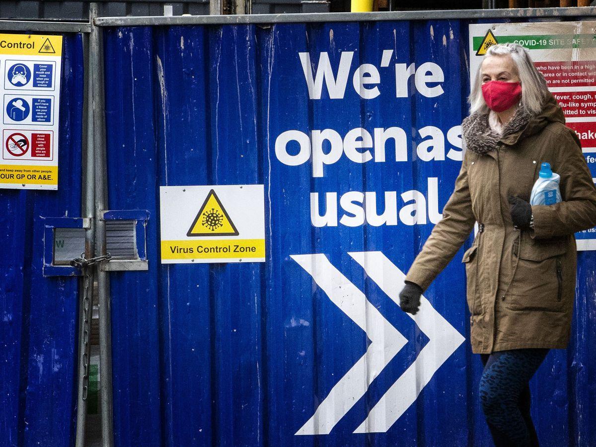 A shopper walks past a coronavirus sign in Edinburgh