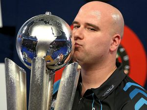 Rob Cross with the World Championship trophy at the start of last year and, below, competing in the Grand Slam of Darts in Wolverhampton     Pictures: Lawrence Lustig/PDC