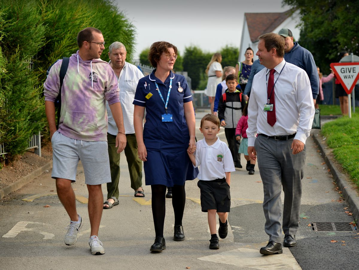 Landywood Primary School headteacher Andrew Clewer welcomes Martin and Amy Hawthorne and five-year-old Oliver