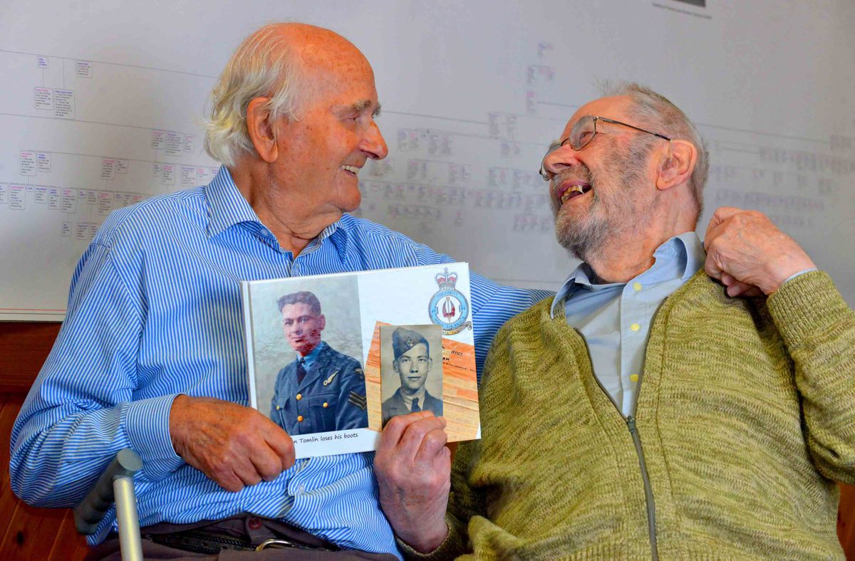 Ron and Roy Tomlin hold photographs of themselves from their RAF days
