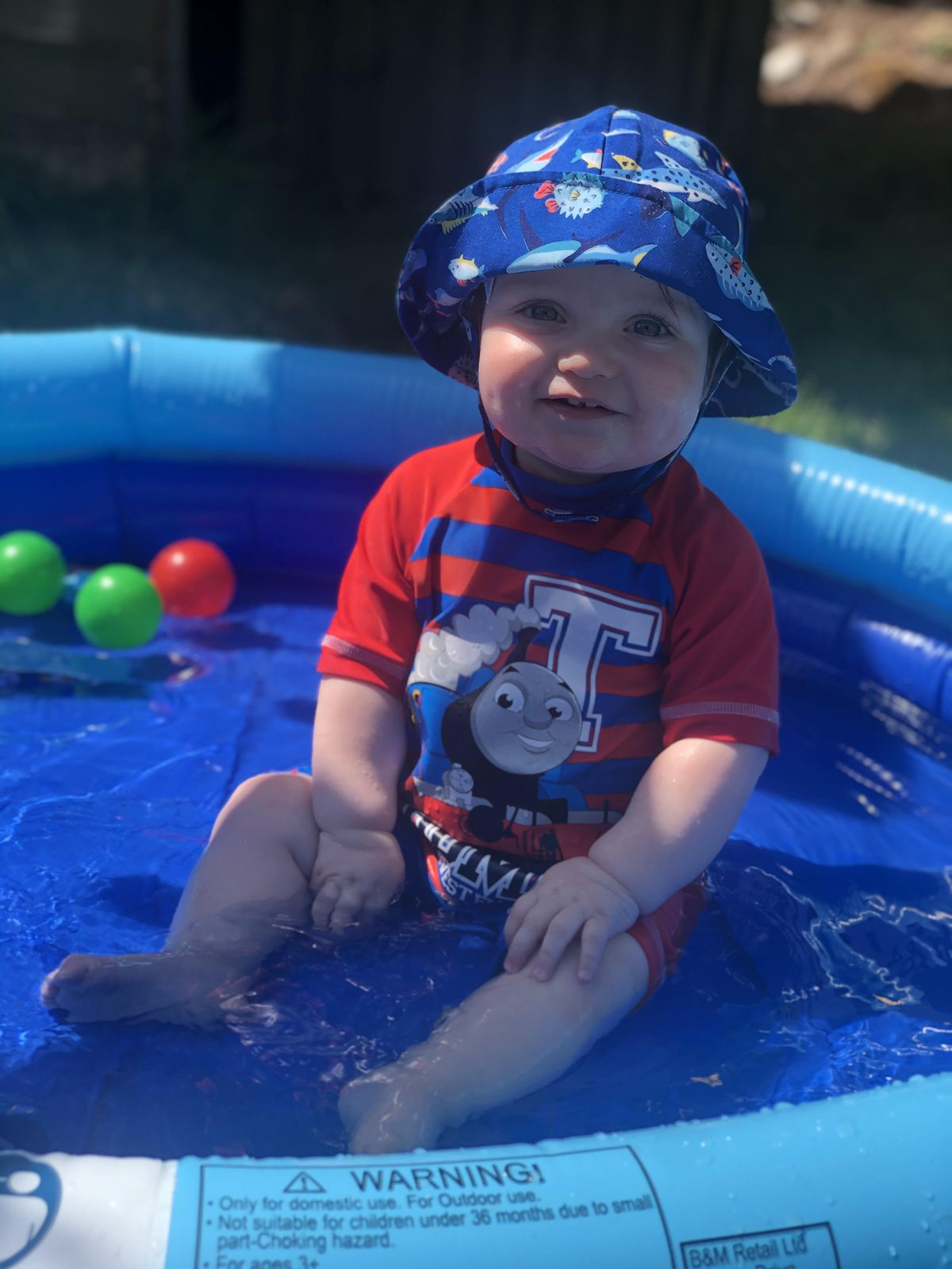 One year-old CJ enjoying the sunny weather in his paddling pool with parents Charlotte andChristopher Sawyer in Upper Tean, Staffordshire