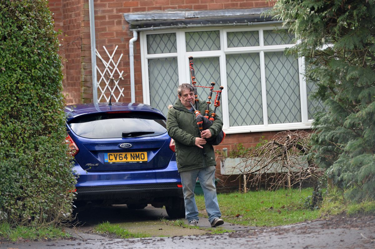 A neighbour of milkman Kieron Moss plays the bagpipes during his funeral procession