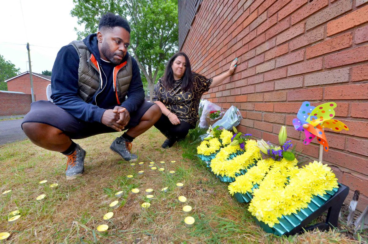 Keelan Wilson's parents, Gary Wilson and Kelly Ellitts with floral tributes left at the scene on the first anniversary of his death