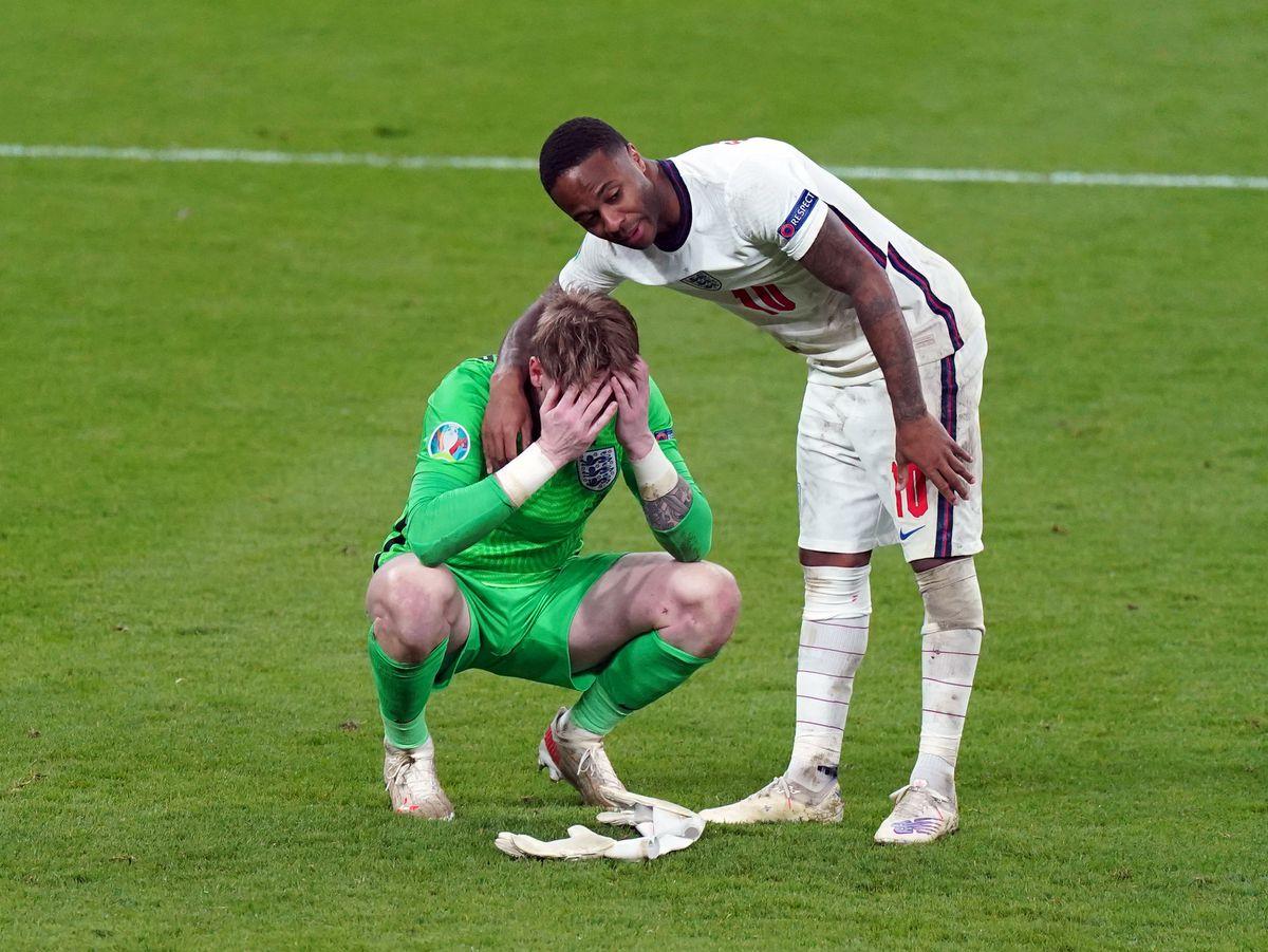 England goalkeeper Jordan Pickford stands dejected with Raheem Sterling